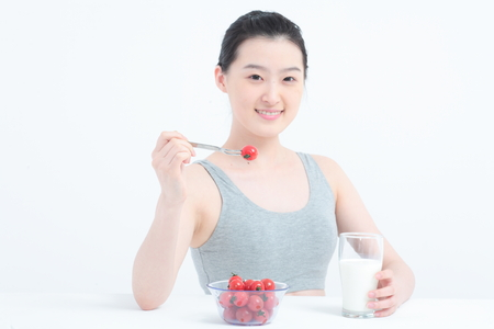 Young Asian woman with cherry tomatoes and a glass of milk - isolated on white