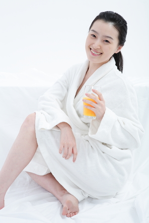 Young Asian woman in bathrobe posing with a glass of orange juice - isolated on white