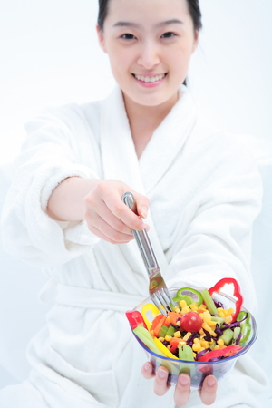 korean salad: Young Asian woman in bathrobe posing with a bowl of salad - isolated on white