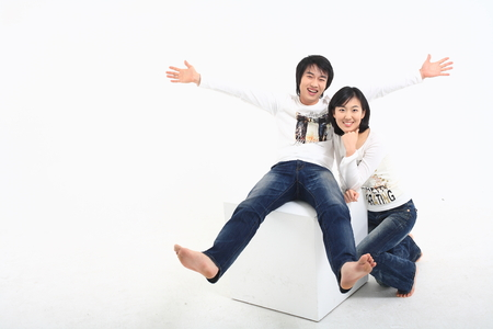 hurray: Young asian couple sitting in studio - isolated on white Stock Photo