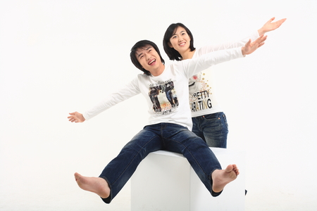 hooray: Young asian couple sitting in studio - isolated on white Stock Photo
