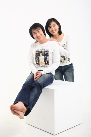 sedentario: Young asian couple sitting in studio - isolated on white Foto de archivo