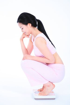 bodycare: Diet concept - Young Asian woman on scale