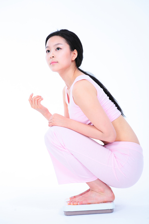 undergarments: Diet concept - Young Asian woman on scale