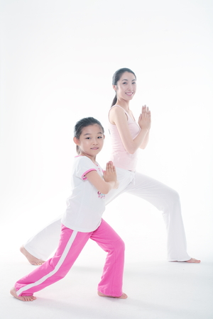 Young Asian mom and her little daughter doing yoga poses together - isolated on white Stok Fotoğraf