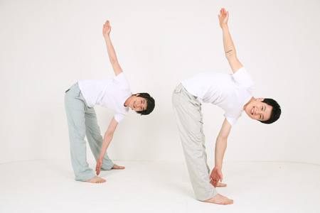 mental activity: Two Asian men doing yoga poses together - isolated on white