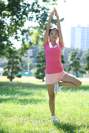 Young Asian woman doing yoga poses in the park Stock Photo