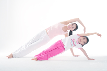 Young Asian mom and her little daughter doing yoga poses together - isolated on white 版權商用圖片