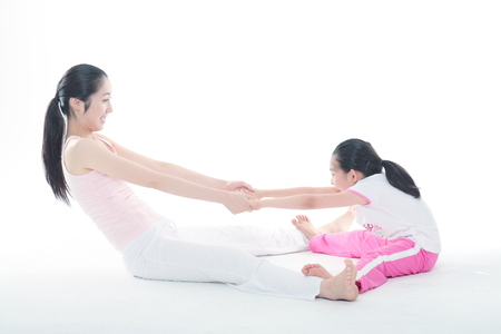 Young Asian mom and her little daughter doing yoga poses together - isolated on white Reklamní fotografie