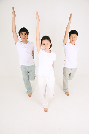 mental activity: Young Asian people doing yoga poses together - isolated on white