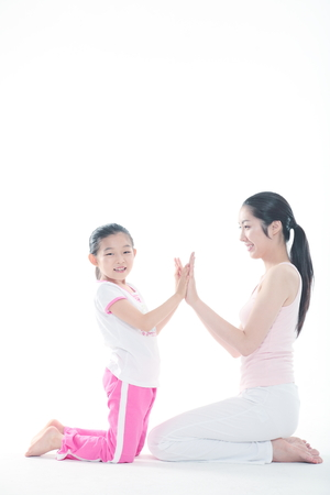 Young Asian mom and her little daughter doing yoga poses together - isolated on white Stock Photo