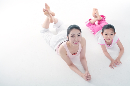 mental activity: Young Asian mom and her little daughter doing yoga poses together - isolated on white Stock Photo