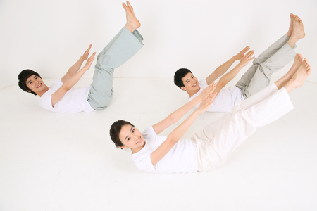 Young Asian people doing yoga poses together - isolated on white