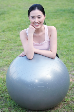 Young Asian woman working out with a gym ball in the park Stock Photo