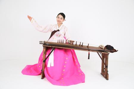 arpa: Mujer asiática con ropa tradicional jugando instrumento musical - aislados en blanco Foto de archivo