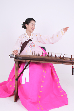 arpa: Asian woman with traditional clothing playing musical instrument - isolated on white Foto de archivo