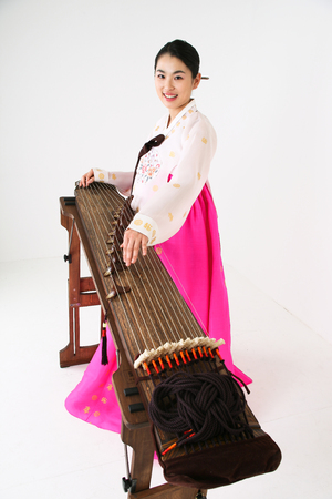 Asian woman with traditional clothing playing musical instrument - isolated on white Stock Photo