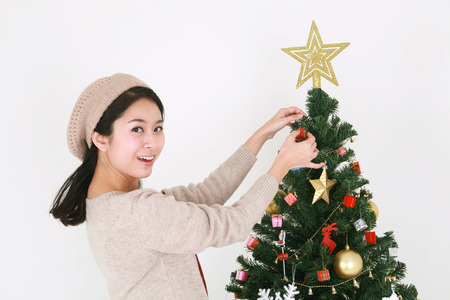 Young korean female student beside christmas tree - isolated on white