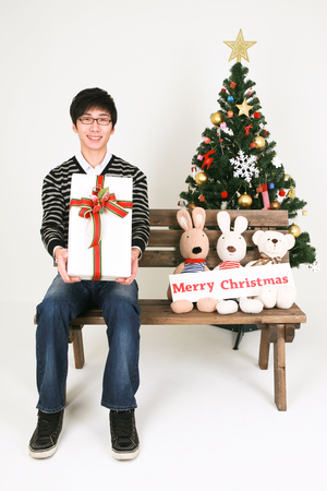 Asian man beside christmas tree - isolated on white