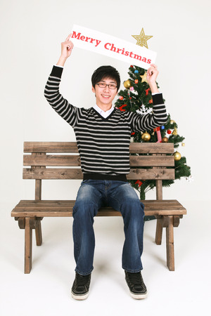 hurray: Asian man beside christmas tree - isolated on white