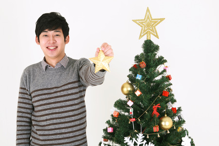 Young korean student beside christmas tree - isolated on white Stock Photo