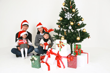 Asian people beside christmas tree - isolated on white