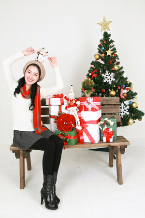 Young korean woman beside christmas tree - isolated on white