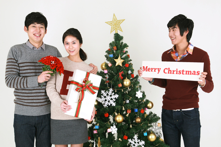 beside: Young korean students beside christmas tree - isolated on white