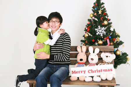 beside: Asian father and daughter beside christmas tree - isolated on white Stock Photo
