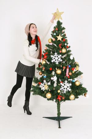 Jonge Koreaanse vrouw naast Kerstboom - geïsoleerd op wit Stockfoto