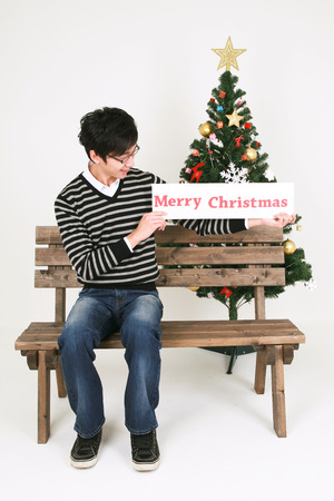 beside: Asian man beside christmas tree - isolated on white