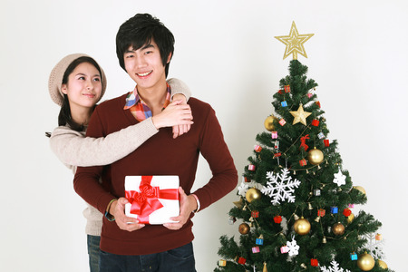 beside: Young korean student beside christmas tree - isolated on white Stock Photo