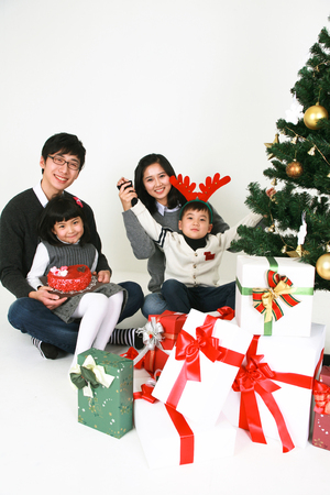 beside: Asian people beside christmas tree - isolated on white