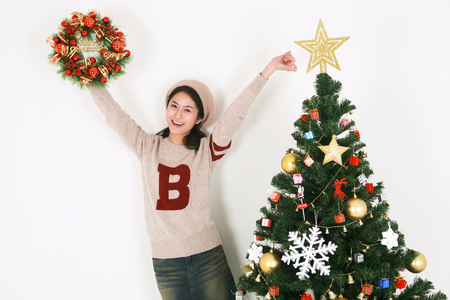 beside: Young korean female student beside christmas tree - isolated on white