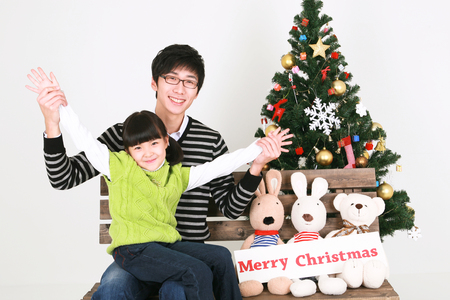 hurray: Asian father and daughter beside christmas tree - isolated on white Stock Photo