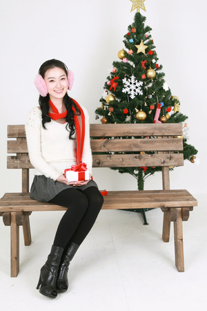 beside: Young korean woman beside christmas tree - isolated on white
