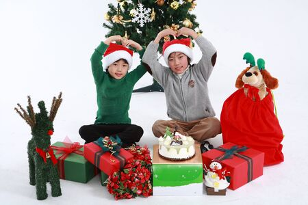 Asian kids with santa outfit and gifts- isolated on white