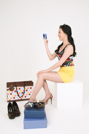 Shopping Concept - Young Asian woman posing with a credit card next to a pair of high heels,gift boxes and shopping bag Editorial