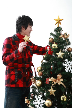 Young asian man near christmas tree - isolated on white