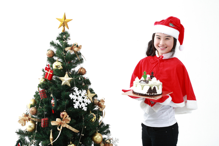 snow man party: Young asian woman with santa hat near christmas tree - isolated on white
