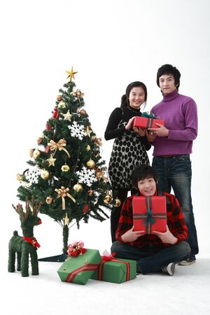 Young asian people near christmas tree - isolated on white