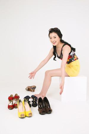 Nakupování koncepce - mladá asijská žena představuje s pár páry vysoké podpatky