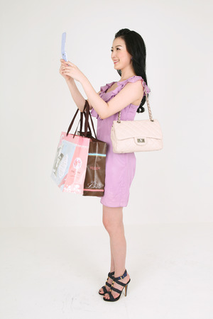 carding: Shopping Concept - Young Asian woman text carding on the cellphone and carrying shopping bags and a purse