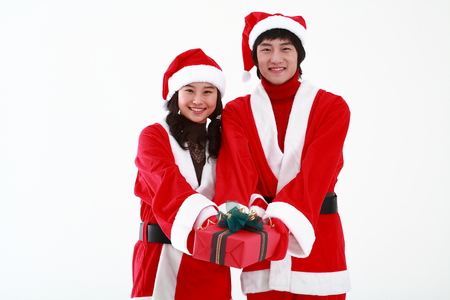 Young asian couple with santa claus outfit - isolated on white Stock Photo