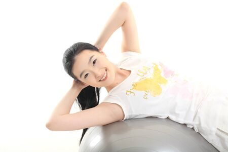 Young Asian woman working out with a gym ball - isolated on white Stock Photo