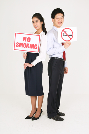 No smoking concept - Young Asian couple posing with no smoking sign