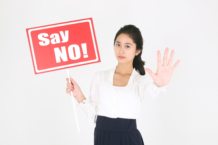 No smoking concept - Young Asian businesswoman holding Say No! sign