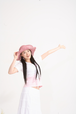 human likeness: Young asian woman wearing big straw hat for picnic concept in studio - isolated on white