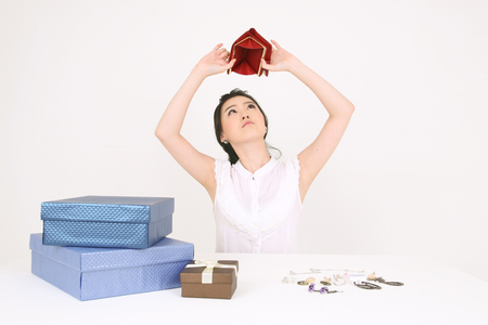 Winkelconcept - Jonge Aziatische vrouw toont haar lege portemonnee met geschenkdozen en accessoires Stockfoto