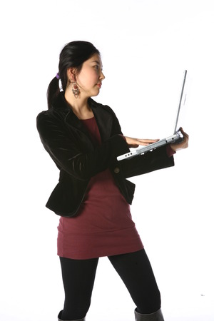 Young asian woman holding up a laptop computer in studio - isolated on white